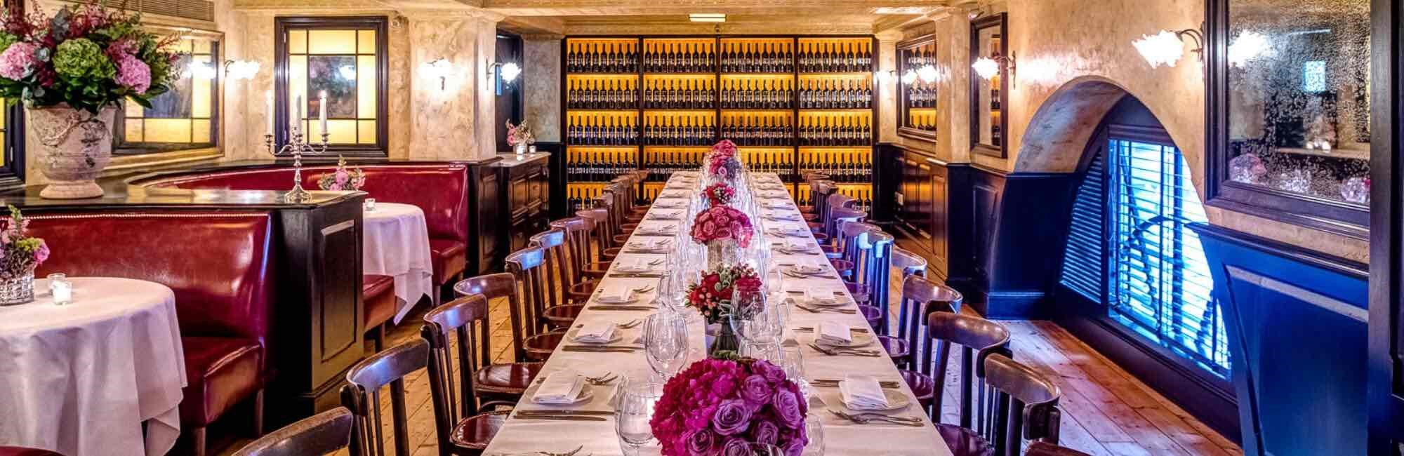 Long table laid for service for large private dining party