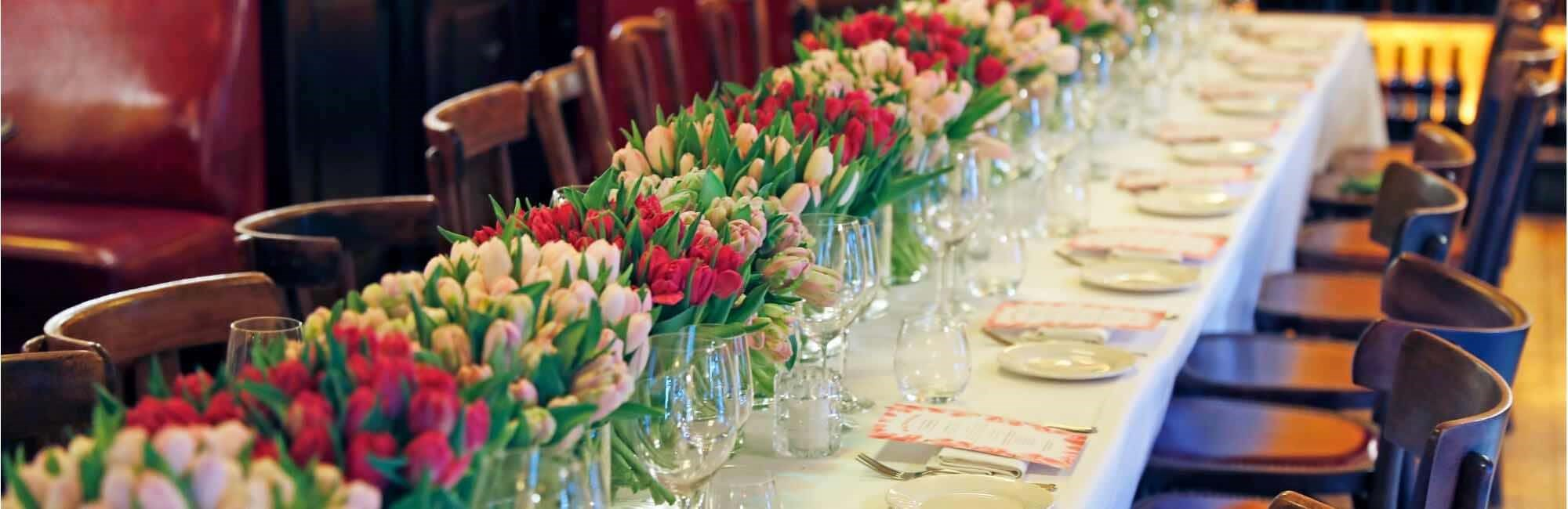 Table with flowers laid for large private dining party