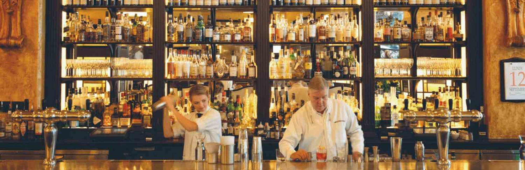 Bartenders shaking and mixing cocktails behind the bar
